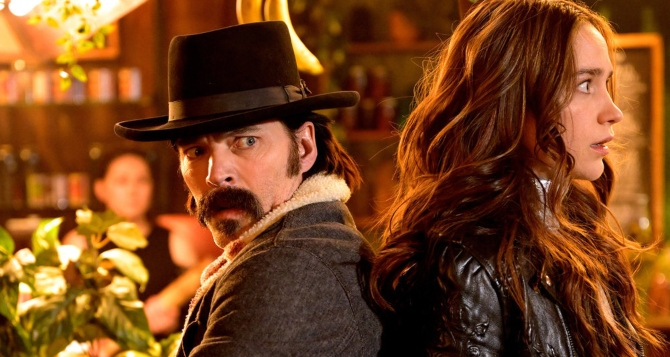 """WYNONNA EARP -- """"Look At Them beans"""" Episode 403 -- Pictured: (l-r) Tom Rozon as Doc Holliday, Melanie Scrofano as Wynonna Earp -- (Photo by: Michelle Faye/Wynonna Earp Productions, Inc./SYFY)"""